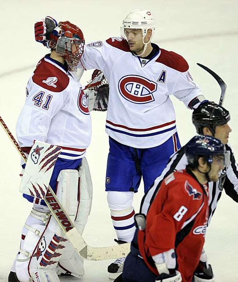 Montreal Canadiens goalie Jaroslav Halak (41), of Slovakia, and Andrei Markov, top right, of Russia, celebrate a 2-1 win as Washington Capitals left wing Alex Ovechkin (8), also of Russia, skates away in Game 5 of the NHL hockey playoffs, Friday, April 23, 2010, in Washington. Photo: Nick Wass, AP