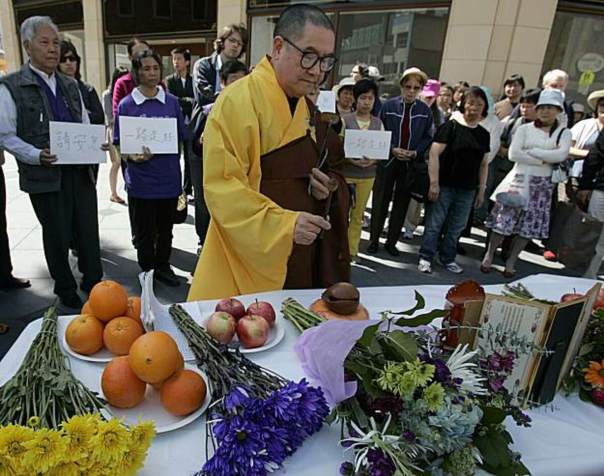 A Buddhist monk offers prayers as he leads a vigil in remembrance of victims Jin Cheng Yu and his 59-year-old father, Tian Sheng Friday, April 23, 2010, in Oakland, Calif. Yu and Sheng were sucker punched by Lavonte Drummer and Dominic Davis on April 16in Oakland, Calif., Sheng died from his wounds.