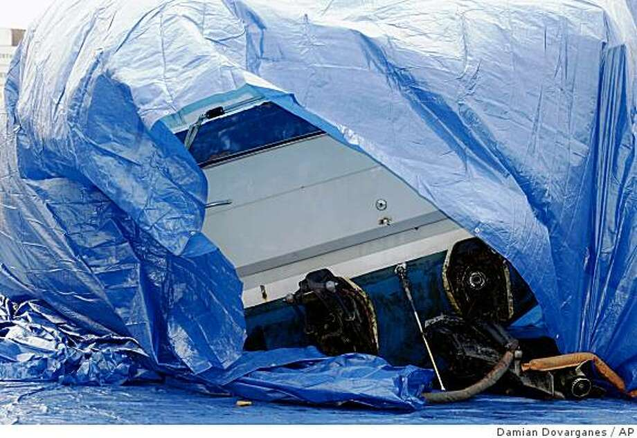 The wreackage of a 26-foot Bayliner pleasure boat is covered with a tarp after being recovered from the ocean floor in the Los Angeles harbor by the U.S. Coast Guard on Thursday, Oct. 9, 2008. Coast Guard and Los Angeles County Sheriff's Department officials confirmed that the bodies also recovered by divers are 51-year-old Henry Sanchez and 48-year-old Penny Avila, the missing brother of two Southern California congresswomen and his girlfriend. (AP Photo/Damian Dovarganes) Photo: Damian Dovarganes, AP