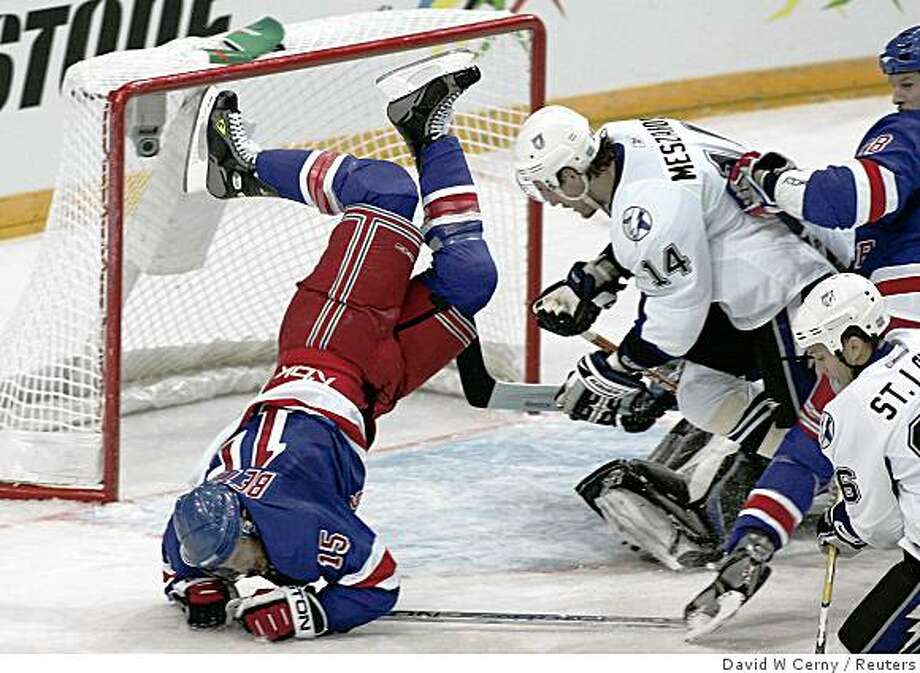 New York Rangers' Blair Betts (L) falls in front of Tampa Bay Lightning's Andrej Mezsaros during their NHL hockey game in Prague October 5, 2008.  REUTERS/David W Cerny (CZECH REPUBLIC) Photo: David W Cerny, Reuters