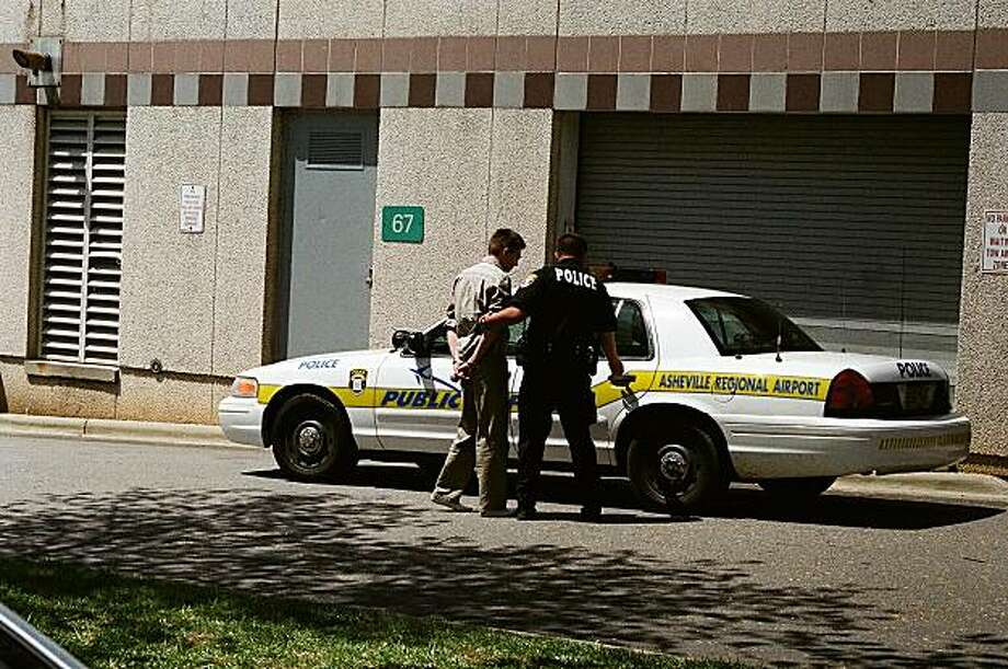 ** CORRECTS SPELLING OF PHOTOGRAPHERS NAME TO HENKELL ** In an Sunday, April 25, 2010 photo provided by Max Henkel, police arrest Joseph McVey, left, charging him with going armed in terror of the public, a misdemeanor, in Asheville, N.C., after authorities spotted him with a gun in a parking lot as Air Force One, with President Barack Obama aboard, was departing.  (AP Photo/Max Henkel) No Sales, No Archives Photo: Max Henkell, AP