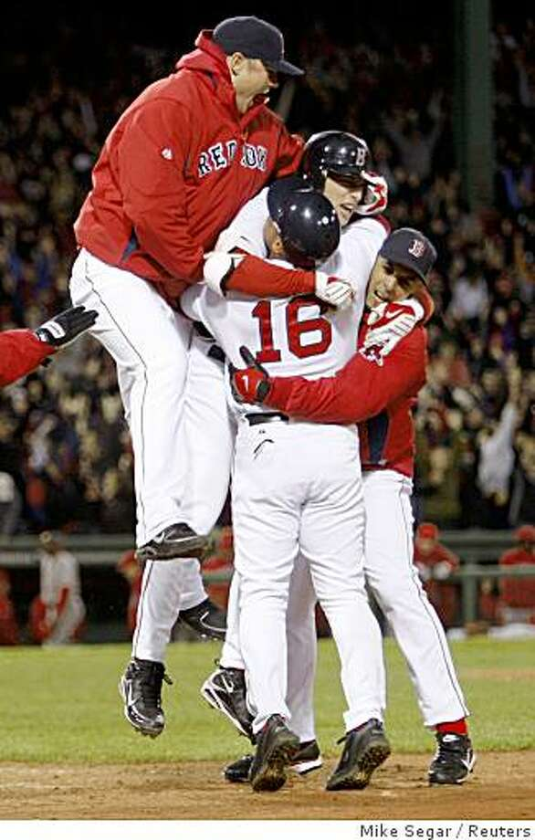 Boston Red Sox Jed Lowrie is congratulated by his teammates after hitting a series winning RBI against the Los Angeles Angels during the ninth inning of Game 4 of their MLB American League Division Series baseball playoff at Fenway Park in Boston, Massachusetts, October 6, 2008.     REUTERS/Mike Segar (UNITED STATES) Photo: Mike Segar, Reuters