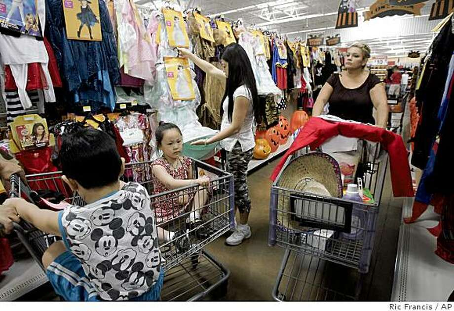 Lorraine Sanchez, right, and Van Ma, second from right, shop at a Wal-Mart Supercenter Thursday, Oct. 2, 2008, in Rosemead, Calif. Retailers' monthly sales reports for September, set to be released Wednesday, are expected to show how the financial meltdown has taken a toll on already fragile consumers. (AP Photo/Ric Francis) Photo: Ric Francis, AP
