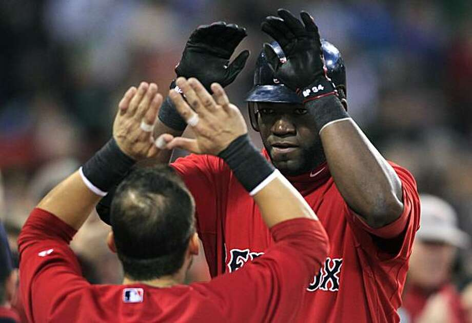 Boston Red Sox designated hitter David Ortiz, right, is congratulated by teammate Marco Scutaro after hitting a solo home run off Baltimore Orioles starter Jeremy Guthrie in the second inning of a baseball game at Fenway Park in Boston, Friday, April 23,2010. Photo: Charles Krupa, AP