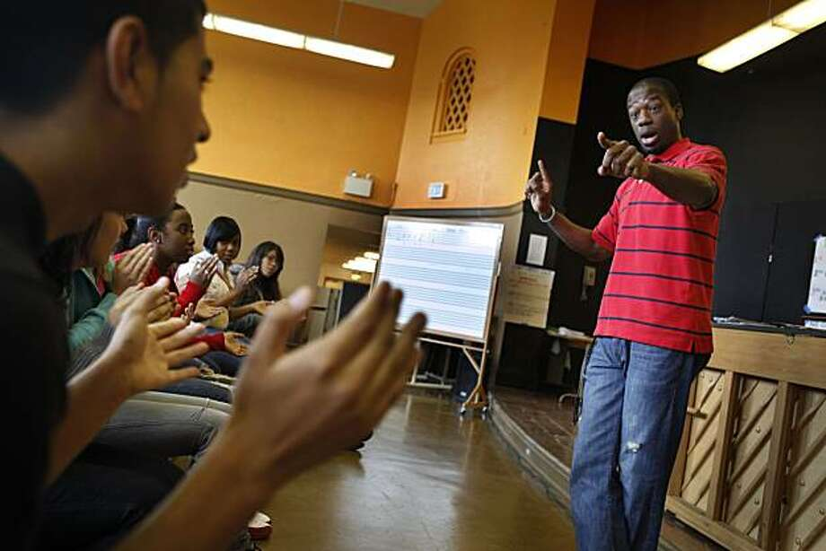 Steven Hankle (right), choir director, works with Ariel Tellez (left), 15, and other students as they clap while they rehearse for an upcoming concert during a choir class at Mission High School in San Francisco, Calif. on Monday April 19, 2010. Photo: Lea Suzuki, The Chronicle