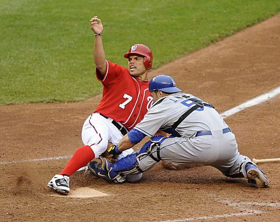Washington Nationals' Ivan Rodriguez (7) reacts as he was tagged out at the plate by Los Angeles Dodgers catcher Russell Martin (55) as Ian Desmond reached on a fielder's choice during the 13th inning of a baseball game, Saturday, April 24, 2010, in Washington. The Dodgers won 4-3 in 13 innings. Photo: Nick Wass, AP