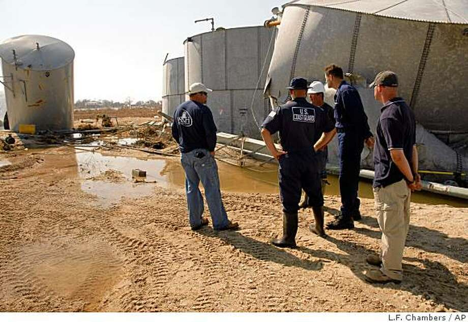 In this photo provided by the U.S. Coast Guard, Unified Command responders discuss conditions at a diesel spill site on Goat Island, Texas, Thursday, Sept. 25, 2008. Teams have been working throughout the Houston-Galveston and Port Arthur, Texas, areas to identify, assess and remediate pollution sites since the passing of Hurricane Ike. (AP Photo/U.S. Coast Guard, Petty Officer 1st Class L.F. Chambers) Photo: L.F. Chambers, AP
