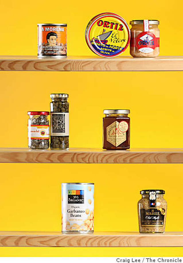 Favorite pantry items clockwise from top: chipotle peppers in adobo, fancy tuna in olive oil, high-quality honey, whole-grain mustard, garbanzo beans, salted capers. Photo: Craig Lee, The Chronicle