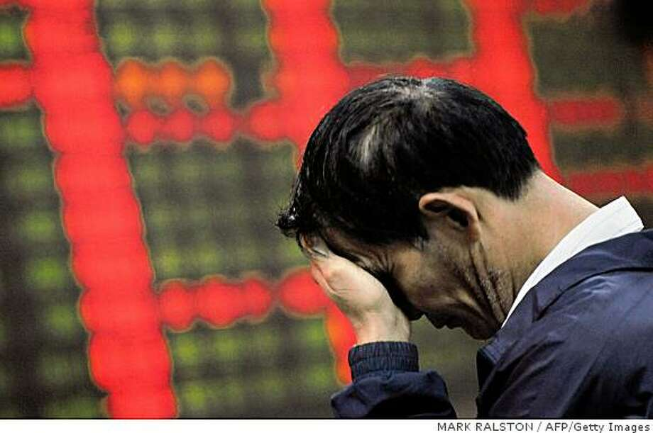 A Chinese investor reacts in front of a stock price board showing falling prices at a private security firm in Shanghai on October 6, 2008.  Chinese share prices closed down 5.23 percent as persistent financial jitters in the United States outweighed news that margin trading would begin on a trial basis. The Shanghai A-share index fell 126.06 points, or 5.23 percent, to 2,282.81 points on turnover of 47.2 billion yuan, while the Shenzhen A-share index was down 24.20 points, or 3.75 percent, to 620.75 on turnover of 21.8 billion yuan.     AFP PHOTO/Mark RALSTON (Photo credit should read MARK RALSTON/AFP/Getty Images) Photo: MARK RALSTON, AFP/Getty Images