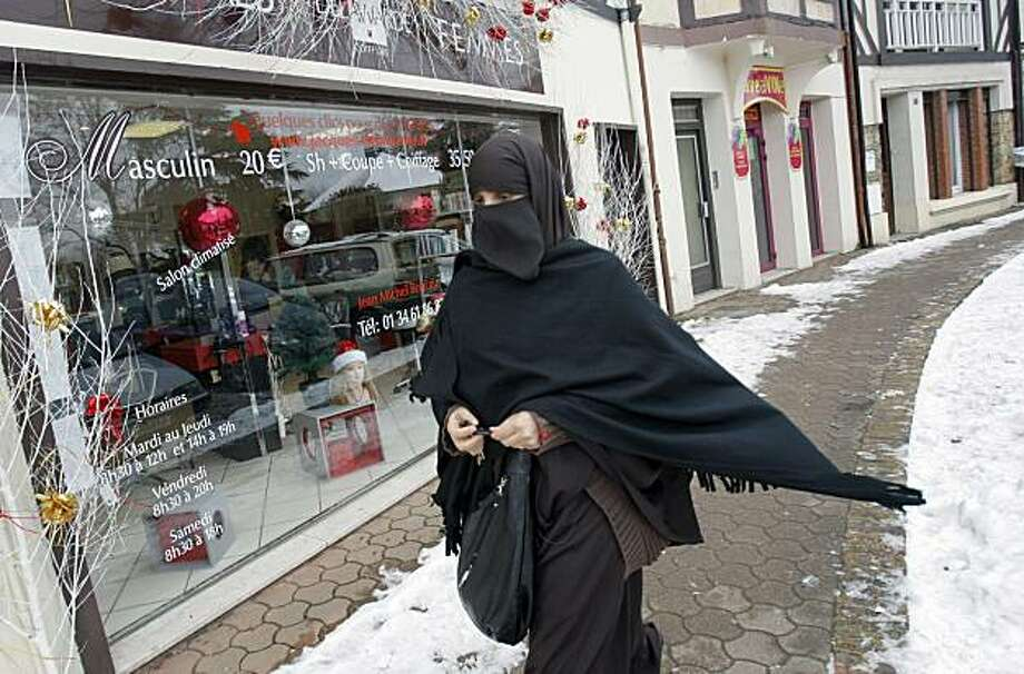 FILE - In this Jan. 12, 2010 file photo, Faiza Silmi, a 32-year-old Moroccan, walks on the street in Le Mesnil-Saint-Denis, 38 kilometers (24 miles) southwest of Paris. French President Nicolas Sarkozy has ordered legislation that would ban women from wearing Islamic veils that fully cover the face and body in public places, the government said Wednesday April 21, 2010. Photo: Christophe Ena, AP