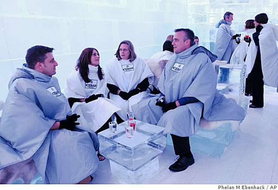 Aaron Mendelson, left, Michelle Smith, Suzanne Stephan and Keith Salwoski, right, relax in warm coats and gloves inside IceBar Orlando in Orlando, Fla., Wednesday, Oct. 1, 2008.  The bar, thought to be the first of its kind in the United States, allows guests to experience 45 minutes in 27-degree temperatures, while sitting on fur-lined ice furniture and enjoying vodka drinks in glassware, also made of ice. (AP Photo/Phelan M. Ebenhack) Photo: Phelan M Ebenhack, AP