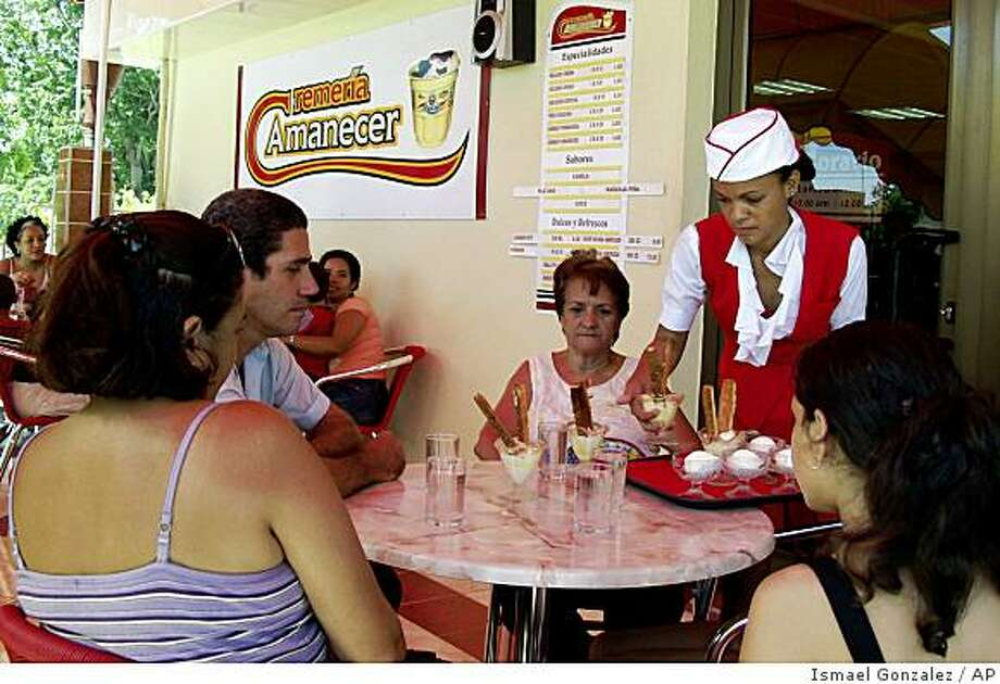 "**APN ADVANCE FOR SUNDAY OCT.5**    A local vendor attends a family at the ""Amanecer"" ice cream in Bayamo, in Granma's province, Wednesday, Aug.6, 2008.In Havana and many other places, businesses charging in convertible pesos outnumber those offering peso fare, meaning lines are longer for those with regular pesos. In Bayamo, the opposite is true: Customers line up outside just two convertible peso stores. Inside are items found nowhere else, including toilet paper, shampoo and imported soaps and perfume.(AP Photo/Ismael Gonzalez, Prensa Latina) Photo: Ismael Gonzalez, AP"