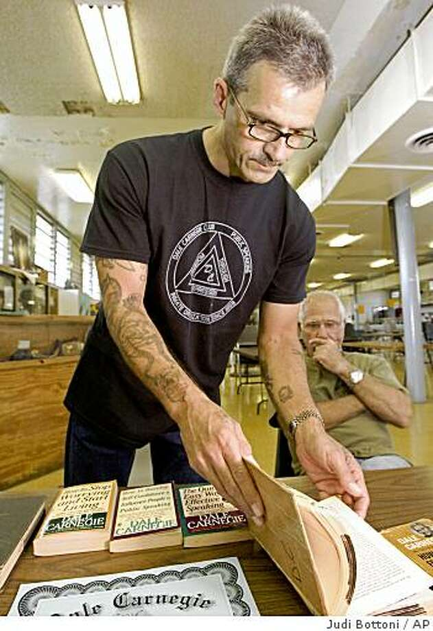 **APN ADVANCE FOR SUNDAY OCT.5**  Mark Burge displays the books used in the Angola Carnegie club  with an Associated Press reporter at the Angola Prison, largest high-security prison in the country in Angola, La. Tuesday August 5, 2008.   (AP Photo/Judi Bottoni) Photo: Judi Bottoni, AP