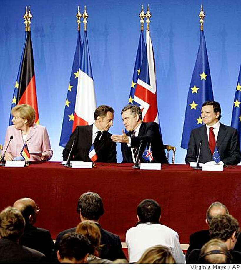 French President Nicolas Sarkozy, center left, shares a word with British Prime Minister Gordon Brown during a media conference at an emergency financial summit at the Elysee Palace in Paris, Saturday Oct. 4, 2008. The global financial crisis is forcing the  leaders of France, Britain, Germany and Italy to come together for an emergency summit in Paris. But differences on how to respond to the economic turmoil could drive them apart. Seated left is German Chancellor Angela Merkel, and right is European Commission President Jose Manuel Barroso. (AP Photo/Virginia Mayo) Photo: Virginia Mayo, AP