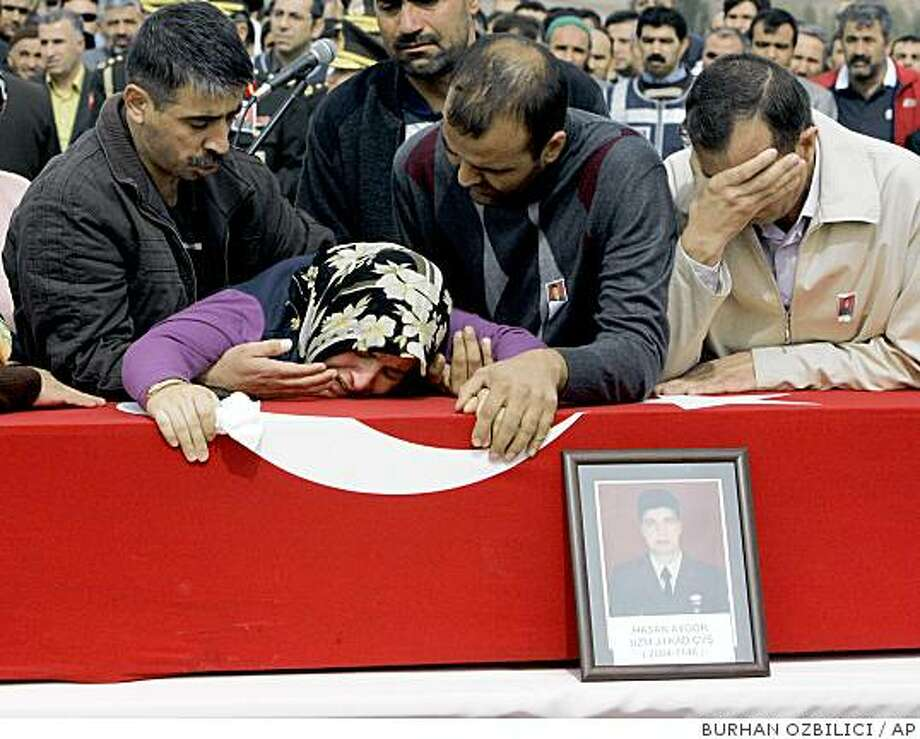 Family members react over the flag-draped coffin of Hasan Aygor, one of 15 Turkish soldiers killed Friday by Kurdish rebels at Turkey-Iraq border, during his funeral in his village of Armutlu, some 130 kilometer east of the captal Ankara, Turkey, Sunday, Oct. 5, 2008. Tens of thousands of Turks in cities across Turkey attended the funerals of slain soldiers. Some mourners booed Prime Minister Tayyip Erdogan in Armutlu and President Abdullah Gul in Eskisehir during the funerals. (AP Photo/Burhan Ozbilici) Photo: BURHAN OZBILICI, AP