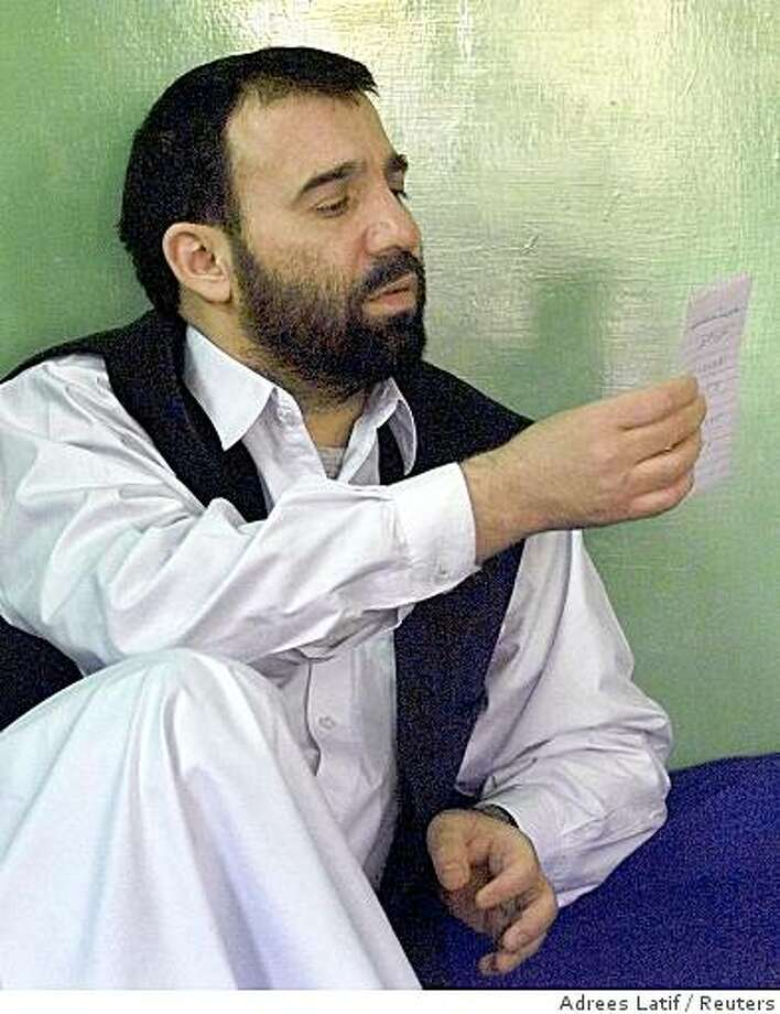 Ahmad Karzai reads a note handed to him during an interview in Quetta, November 3, 2001. Ahmad Karzai denied reports that his brother Hamid Karzai, a supporter of ex-King Zahir Shah, was arrested by the Taliban while trying to summon support for a broad-based post-Taliban government in the Oruzgan province of Afghanistan. REUTERS/Adrees Latif Photo: Adrees Latif, Reuters
