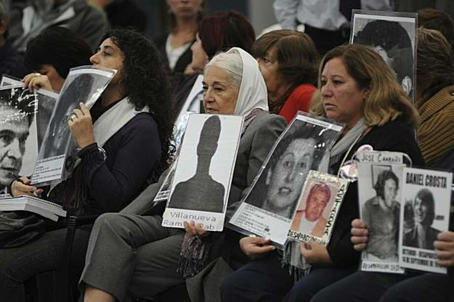 Protesters hold images of disappeared people at a courthouse where Argentina's last dictator is on trial on the outskirts of Buenos Aires, Tuesday, April 20, 2010. A judge will read the verdict in a trial of former Gen. Reinaldo Benito Bignone, five former generals and two others, who are accused of kidnappings and murders in one of the nation's largest torture centers, the Campo de Mayo military base.  Bignone is accused of holding ultimate responsibility for cases of torture, illegal break-ins and deprivations of freedoms from 1976 to 1978, before he was appointed president by the military junta in the waning years of the dictatorship (1982-1983). Photo: Rolando Andrade Stracuzzi, AP