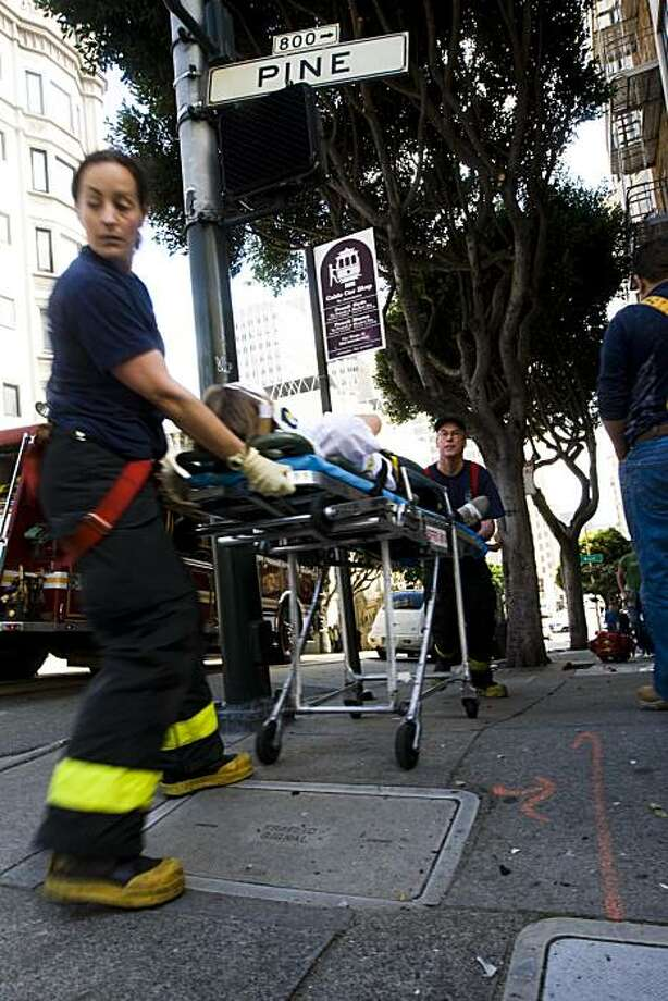 Paramedics take David Dokter, an architecture student from Austria, to an ambulance after he was hit by a car involved an in accident Monday in San Francisco. Photo: Ali Thanawalla, The Chronicle