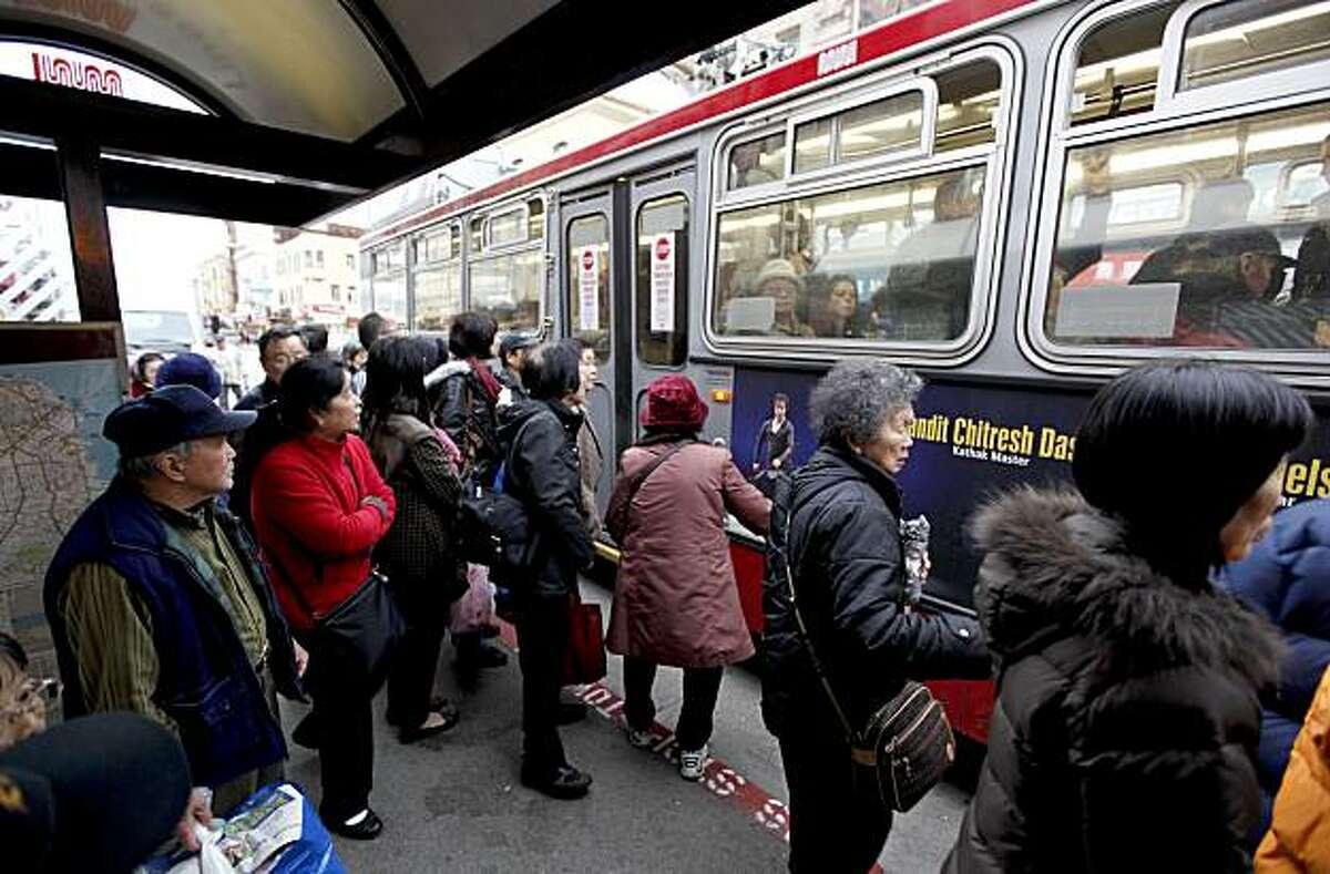 Riders scramble onto a Muni bus stopped along Stockton Street near Broadway on Friday.