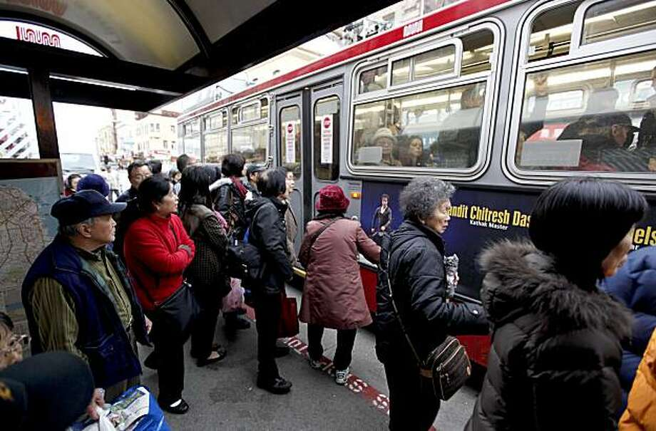 Riders scramble onto a Muni bus stopped along Stockton Street near Broadway on Friday. Photo: Michael Macor, The Chronicle
