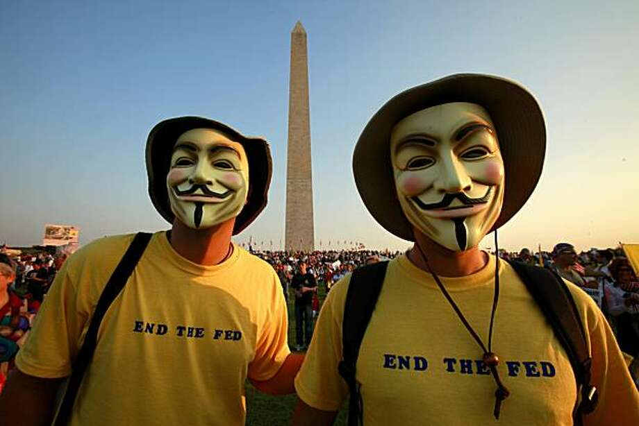 "** HOLD FOR RELEASE AT 8 P.M. ON SUNDAY, APRIL 18, 2010, AND THEREAFTER ** FILE - In this April 15, 2010 file photo, two men who asked to be called only, ""Guy Fawkes,"" attend a tea party rally at the Washington Monument in Washington. Can you trust Washington? Nearly 80 percent of Americans say they can't and they have little faith in the massive federal bureaucracy solving the nation's ills, according to a new survey from the Pew Research Center that shows confidence in the federal government at one of the lowest points in half century. Photo: Jacquelyn Martin, AP"