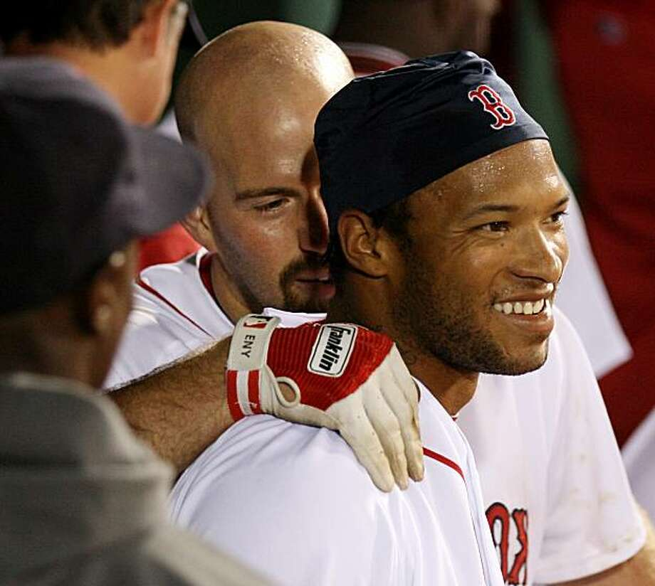 Boston Red Sox's Darnell McDonald, right, is hugged in the dugout by teammate Kevin Youkilis after McDonald's two-run home run tied the game during the eighth inning against the Texas Rangers in a MLB baseball game at Fenway Park in Boston Tuesday, April20, 2010. Photo: Winslow Townson, AP