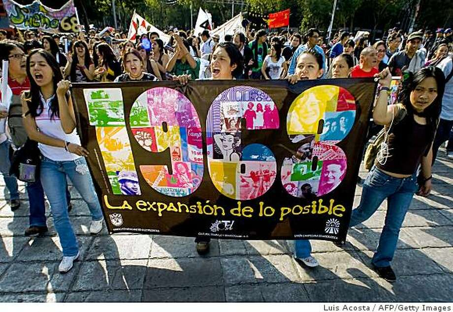 "Students hold a banner reading ""1968, The expansion of the possible"", as they take part in a march during the anniversary of the massacre of Tlatelolco, in Mexico City, on October 2, 2008. Mexico commemorates the 40th anniversary of a deadly clampdown on student protestors this week with the details of the massacre still unclear, the perpetrators untried, and impunity as widespread as ever. As student movements shook the world in 1968, Mexican security forces killed at least 44 protesting students in the country's capital 10 days before the start of the Olympics here, and rapidly cleared up the evidence. AFP PHOTO/Luis Acosta (Photo credit should read LUIS ACOSTA/AFP/Getty Images) Photo: Luis Acosta, AFP/Getty Images"