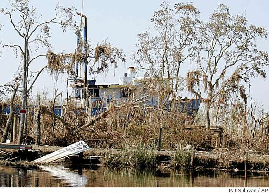 A large boat sits in the dead trees and grass along with other debris Tuesday, Sept. 30, 2008 in the middle of a destroyed fishing camp in Trinity Bay near Anahuac, Texas. Much of the debris was blown by Hurricane Ike from Bolivar Peninsula miles across the bay. Dozens of people are still missing more than two weeks after Ike's assault on Texas, and the search for bodies continues.  (AP Photo/Pat Sullivan) Photo: Pat Sullivan, AP