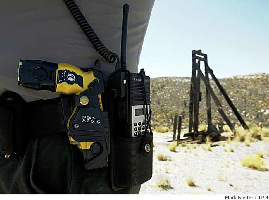 "On the job, Ranger Tim Duncan carries a handgun and a Taser. Next to him in his truck are a shotgun and an M-16 assault rifle with extra magazines. ""Out here, you have to be prepared,"" he says. Illustrates DESERT-RANGER (category a) by Mike Anton (c) 2008, Los Angeles Times. Moved Friday, Sept. 26, 2008. (MUST CREDIT: Los Angeles Times photo by Mark Boster.) Photo: Mark Boster, TPN"