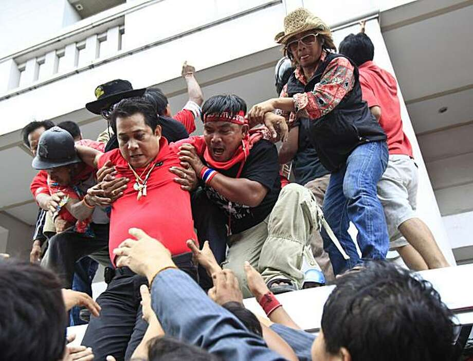 "Anti-government leader Arisman Pongruanrong, in red, is helped by others as he flees arrest Friday, April 16, 2010, at a downtown Bangkok, Thailand, hotel.  Arisman scaled down the facade of the hotel in downtown Bangkok into a waiting crowd of ""Red Shirt"" supporters who then helped him into a car that drove away. Photo: Wong Mayee, AP"