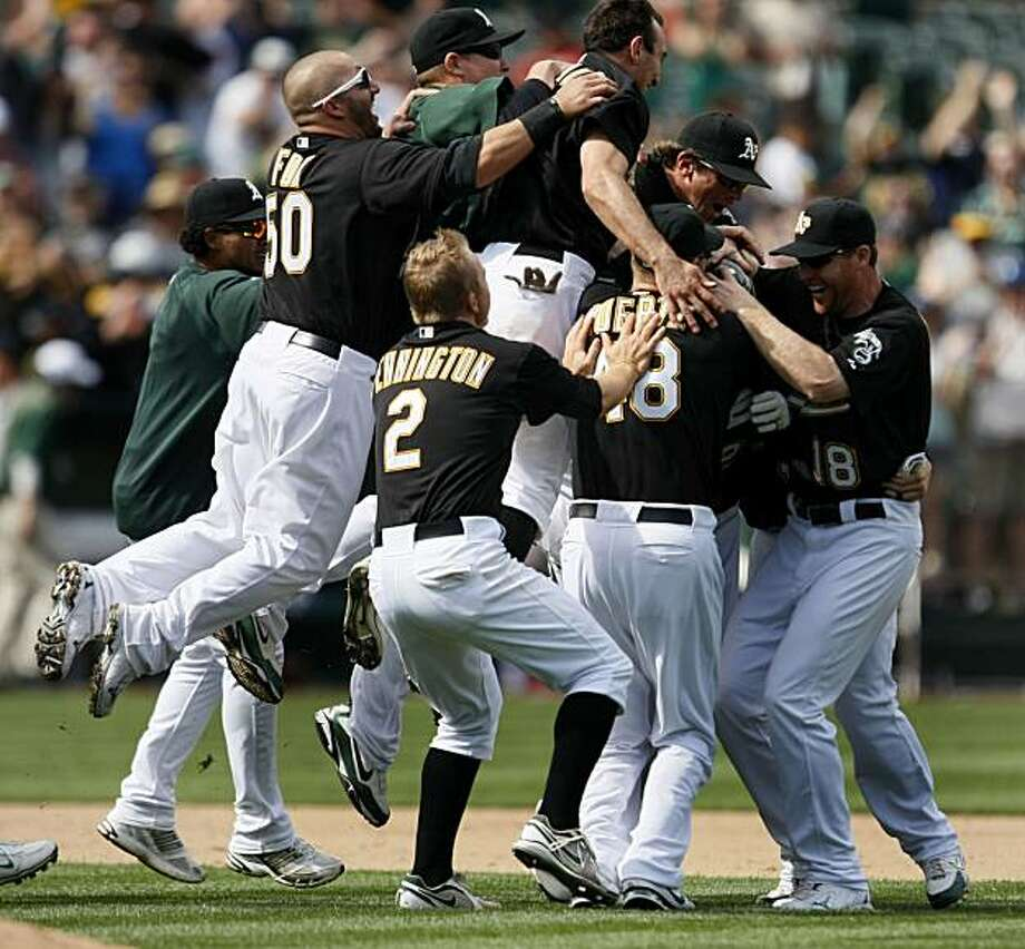 The Oakland A's jump on teammate Ryan Sweeney after his two run single in the ninth inning that won their game over the Baltimore Orioles Saturday in Oakland. Photo: Lance Iversen, The Chronicle