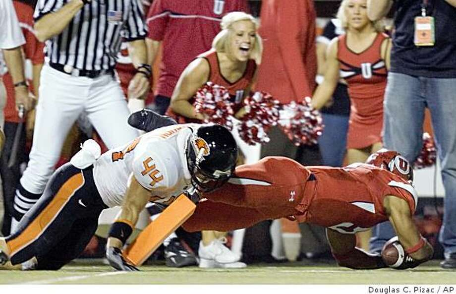 Utah wide receiver Brent Casteel scores against Oregon State's Greg Laybourn (44) with a dive across the goal line during the second quarter of an NCAA college football game Thursday, Oct. 2, 2008, in Salt Lake City. (AP Photo/Douglas C. Pizac) Photo: Douglas C. Pizac, AP