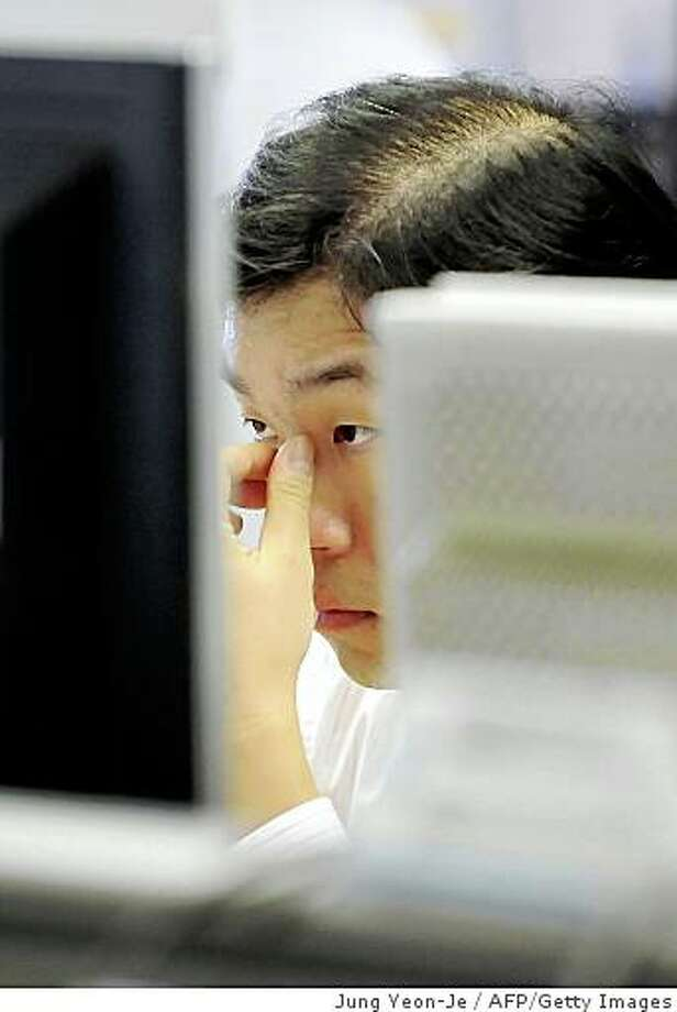 A South Korean dealer looks at a computer screen inside the dealing hall at the Korean Exchange Bank in Seoul on September 30, 2008. The South Korean currency, the won, tumbled against the US dollar trading at 1,223.6 won down 34.8 won from the previous day's close. The currency hit a 57-month low against the greenback and has lost around 30 percent against the US unit since the start of this year. AFP PHOTO/JUNG YEON-JE (Photo credit should read JUNG YEON-JE/AFP/Getty Images) Photo: Jung Yeon-Je, AFP/Getty Images