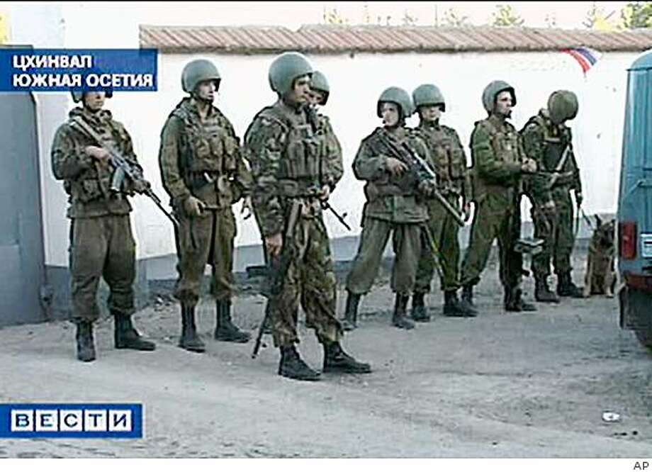 Russian soldiers stand on guard at the Russian military's headquarters after a car explosion in Tskhinvali, capital of the breakaway Georgian region of South Ossetia, Friday, Oct. 3, 2008. A car exploded outside the Russian military's headquarters in South Ossetia on Friday,  the government of the Moscow-backed separatist region in Georgia said. (AP Photo/RTR-Russian Television Channel) ** TV OUT ** Photo: AP