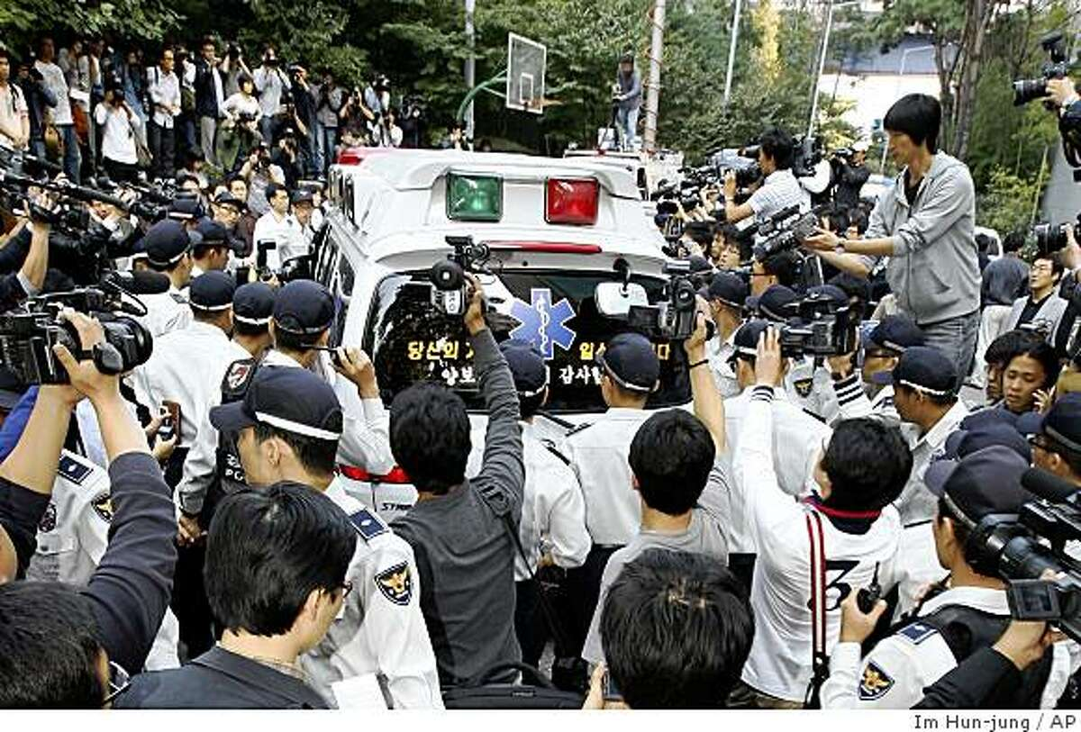 An ambulance carrying the body of top South Korean actress Choi Jin-sil leaves her home for a hospital as surrounded by media and police officers in Seoul, South Korea, Thursday, Oct. 2, 2008. A top South Korean actress has been found dead in a suspected suicide. (AP Photo/Yonhap, Im Hun-jung) ** KOREA OUT **