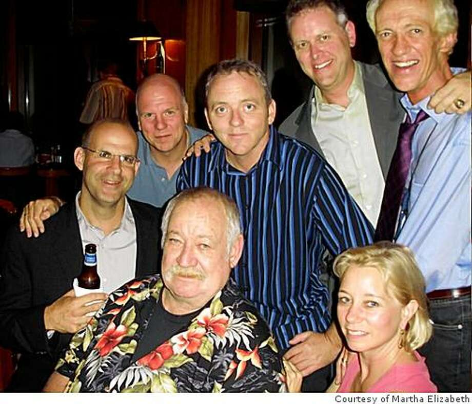 The King and his Court: James Crumley (in Hawaiian shirt) feted in a Toronto tavern by author/acolytes (l-r) Harlen Coben, Peter Robinson, Dennis Lehane, Eddie Muller, Laura Lippman, and Ken Bruen. / Courtesy of Martha Elizabeth Photo: Courtesy Of Martha Elizabeth