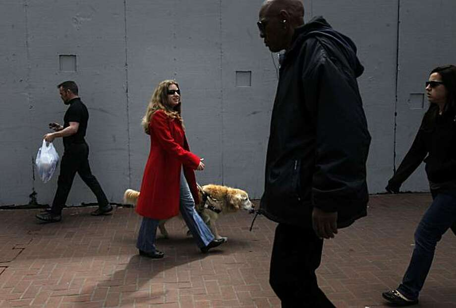 Blind since birth, Courtney Mazzola, 28, walks with her dog Tess down Market Street after an afternoon of errands on April 1, 2010 in San Francisco, Calif. Photo: Mike Kepka, The Chronicle