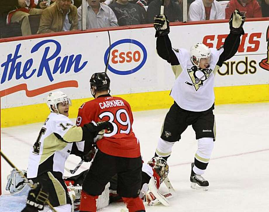 Pittsburgh Penguins captain Sydney Crosby (87) celebrates his teams first goal along with teammate Chris Kunitz, left, against the Ottawa Senators, as Matt Carkner looks on, during the first period of a first-round NHL playoff hockey game in Ottawa, Tuesday April 20, 2010. Photo: Fred Chartrand, AP