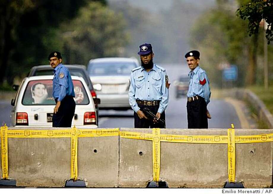 Pakistani police officers stand guard at a checkpoint set up on a road in Islamabad, Pakistan, on Thursday, Oct. 2, 2008. The U.N. ordered children of its international staff to leave the Pakistani capital and other areas it considered unsafe, raising its security level following the bombing of the Marriott Hotel, the world body said Thursday. (AP Photo/Emilio Morenatti) Photo: Emilio Morenatti, AP
