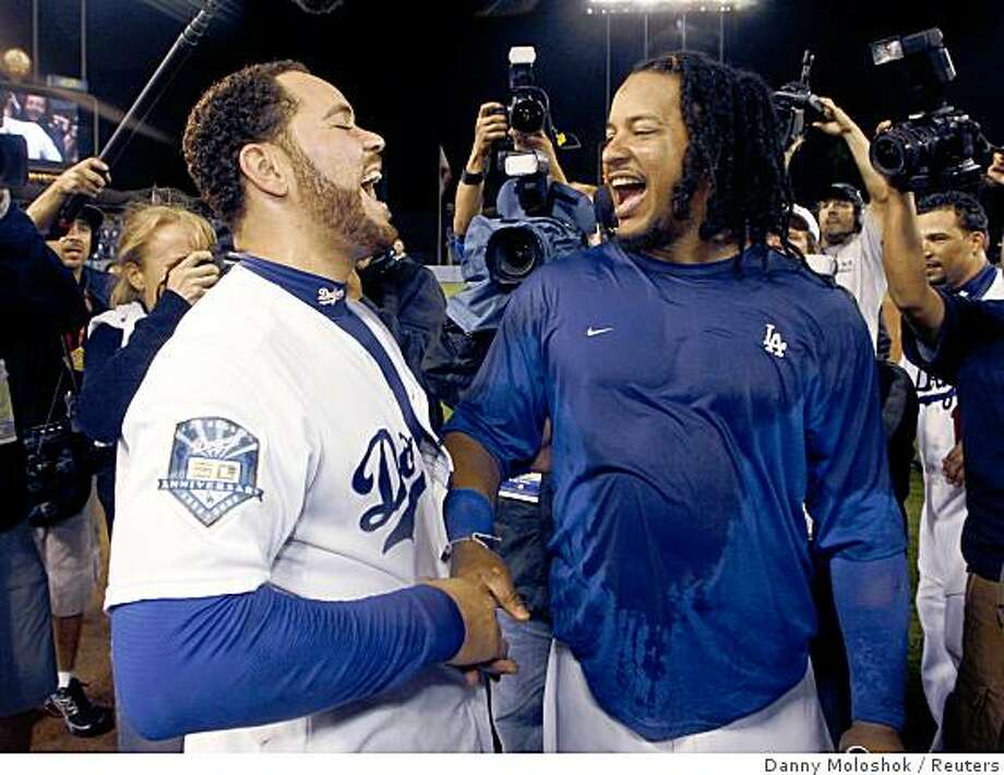 Los Angeles Dodgers Manny Ramirez and teammate Russell Martin (L) celebrate after sweeping the Chicago Cubs to win Game 3 of their MLB National League Divisional Series playoff baseball game in Los Angeles October 4, 2008.     REUTERS/Danny Moloshok (UNITED STATES) Photo: Danny Moloshok, Reuters