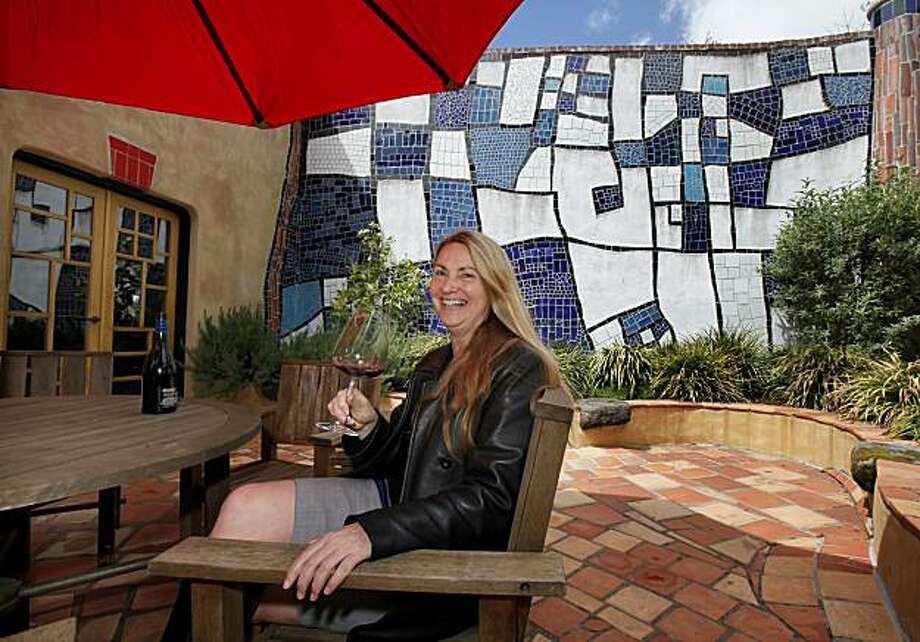 Anne White, the Irish tasting room manager, sits on the patio area where tastings often occur. The Quixote Winery has a totally unique architecture at their location off the Silverado Trail in Napa, Calif. Photo: Brant Ward, The Chronicle