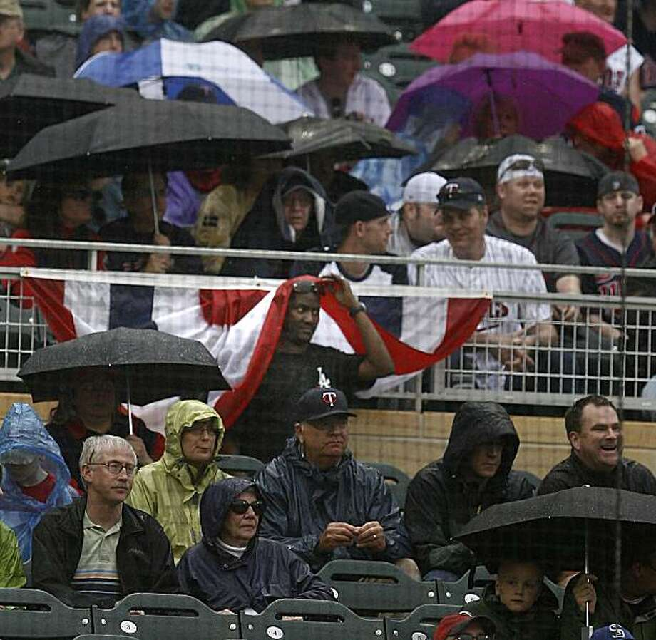 Fans took cover as the rain fell on the game between the Minnesota twins and the Boston Red Sox at Target Field in Minneapolis, Minnesota, Wednesday, April 14, 2010. (Elizabeth Flores/Minneapolis Star Tribune/MCT) Photo: Elizabeth Flores, MCT