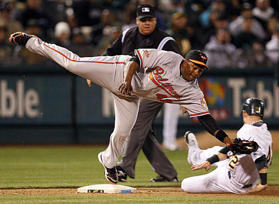 Baltimore Orioles third baseman Miguel Tejada, top, dives to make a catch as Oakland Athletics' Daric Barton advances to third base on a wild pitch from Orioles' Mark Hendrickson during the seventh inning of a baseball game Thursday, April 15, 2010, in Oakland, Calif. Photo: Ben Margot, AP