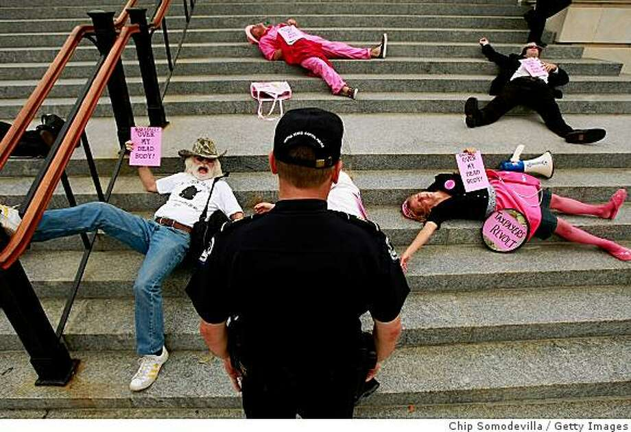 WASHINGTON - SEPTEMBER 29:  A U.S. Capitol Police officer tells demonstrators from the group Code Pink to move from the steps in front of the Cannon House Office Building on Capitol Hill September 29, 2008 in Washington, DC. The 10 demonstrators were voicing opposition to the $700 billion bailout plan for Wall Street worked out between Congress and the Bush Administration.  (Photo by Chip Somodevilla/Getty Images) Photo: Getty Images