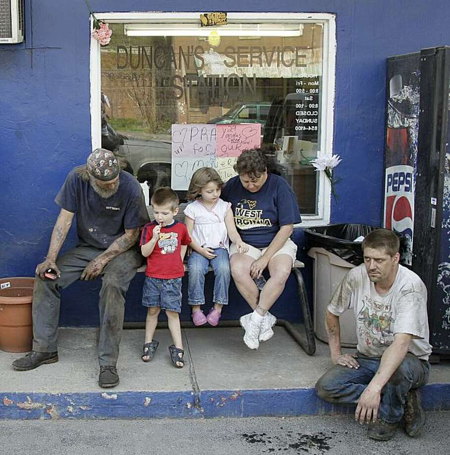 From left, Jerry Beanfield, Jaden Clemons, 3, his sister Gabrielle Clemons, 4, their grandmother Gladys Clemons, and Jerry's brother Randy Bearfield take part in a national moment of silence in honor of the 29 miners who died in the explosion at Massey Energy Co.'s Upper Big Branch mine in Montcoal, W. Va. a week ago Monday, at Duncan's Service Station in Whitesville, W.Va. on Monday, April 12, 2010. Photo: Amy Sancetta, Associated Press