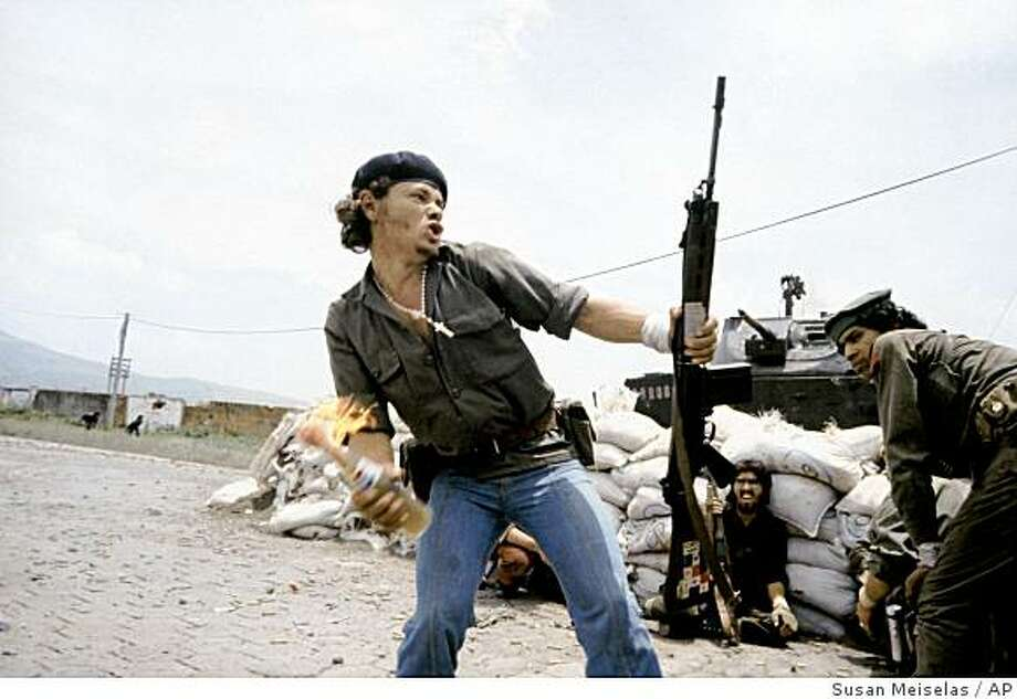 In this image released by the International Center of Photography (ICP), a 1979 photograph by Susan Meiselas shows Sandinistas at the walls of the Esteli National Guard headquarters in Esteli, Nicaragua. The photo is part of an exhibition of Susan Meiselas' work at ICP in New York, through Jan. 4. (AP Photo/ICP, Susan Meiselas) Photo: Susan Meiselas, AP