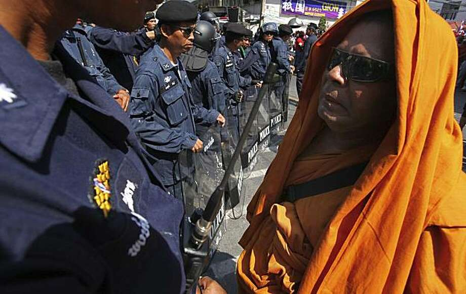 A Buddhist monk stands in front of riot policemen while protest in front of the residence of Thai Prime Minister Abhisit Vejjajiva, Monday, April 12, 2010, in Bangkok, Thailand. The Red Shirt protesters are calling for Abhisit to dissolve parliament and step down. Weekend clashes between anti-government demonstrators and soldiers have left 21 dead and more than 800 injured. Photo: Wason Wanichakorn, Associated Press