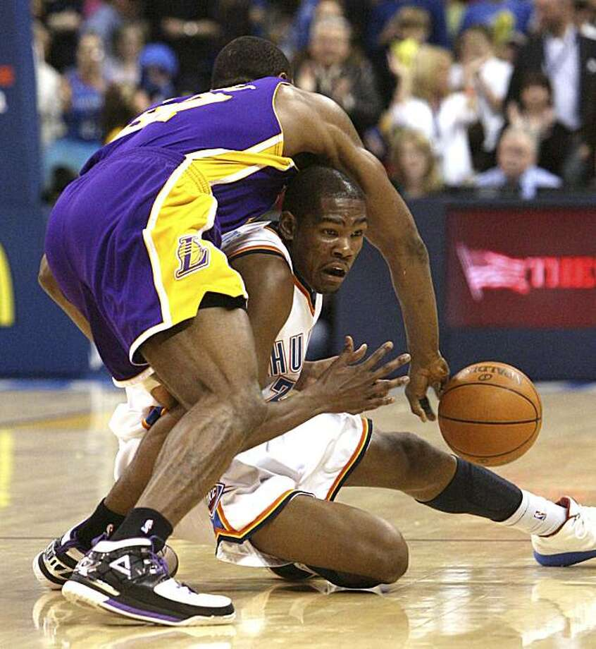 Oklahoma City Thunder forward Kevin Durant, right, falls as he attempts to drive around Los Angeles Lakers forward Ron Artest, left, in the third  quarter of an NBA basketball game in Oklahoma City, Friday, March 26, 2010. Durant had 26 points as OklahomaCity won 91-75. Photo: Sue Ogrocki, AP