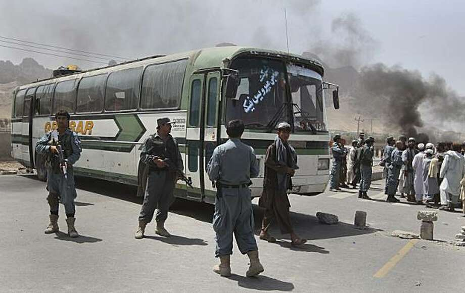 Afghan policemen and protesters stand near a bus after it was fired upon by international troops during a anti-American protest in Kandahar, south of Kabul, Afghanistan, Monday, April 12, 2010. International troops opened fire on a bus carrying Afghan civilians early Monday, killing four people and setting off anti-American protests in a southern city that is a hotbed of the Taliban insurgency. Photo: Allauddin Khan, AP