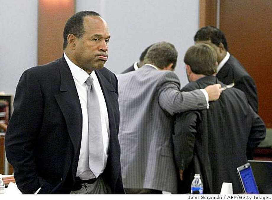 "O.J. Simpson is shown during his trial as co-defendant Clarence ""C.J."" Stewart confers with his attorneys in the background at the Clark County Regional Justice Center Oct. 1, 2008 in Las Vegas, Nev. Photo: John Gurzinski, AFP/Getty Images"